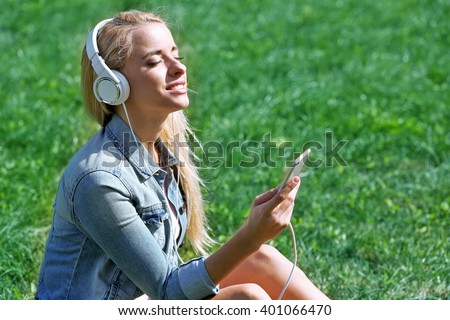 Young woman with earphones and smartphone listening to music on grass - stock photo