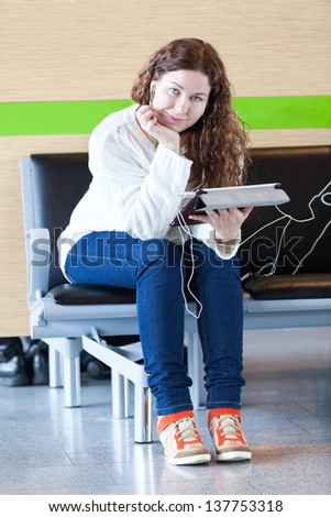 Young woman with electronic devices sitting on chair - stock photo
