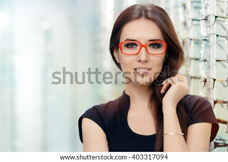 Young Woman with Eyeglasses in Optical Store - Beautiful girl wearing glasses in optician shop  - stock photo