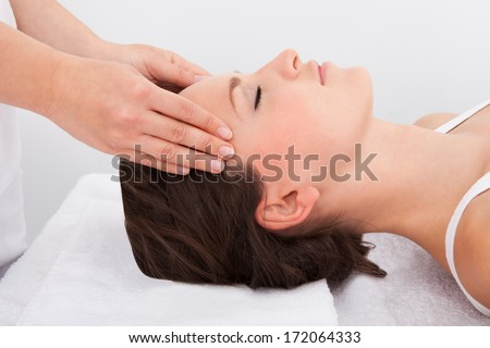 Young Woman With Eyes Closed Getting Massage Treatment From Masseuse
