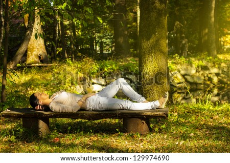 Young woman with eyes closed relaxing on a bench in nature - stock photo