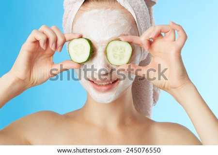 Young woman with facial mask on blue background - stock photo