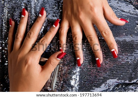 Young woman with fashion red nails against silver sequin background - stock photo