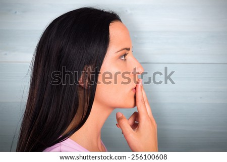 Young woman with finger on lips against bleached wooden planks background