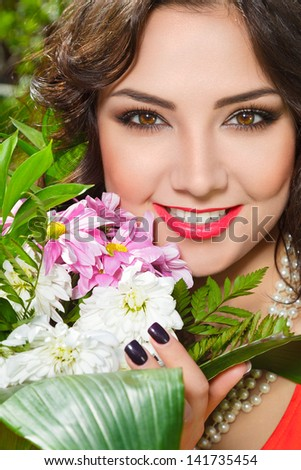 Young woman with flowers in a garden outdoor portrait