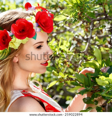 Young woman with flowers in a garden outdoor portrait - stock photo