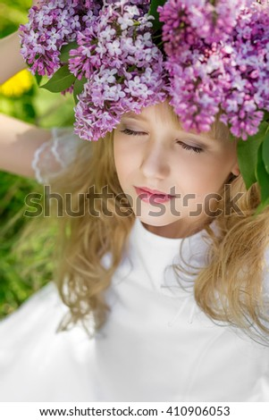 Young woman with flowers in green park. Young girl in beautiful wreath of lilac flowers