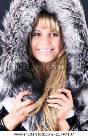Young woman with fluffy hood. On dark background. - stock photo