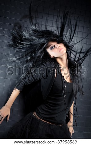 Young woman with fluttering hair. On dark wall background. - stock photo