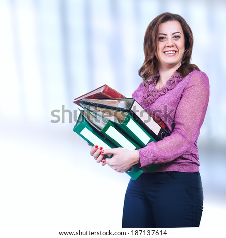Young woman with folders in hand on light blue background - stock photo
