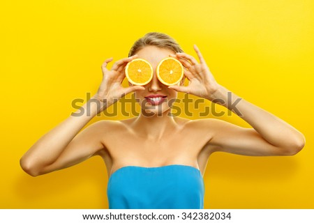 Young woman with fresh fruits on bright orange background - stock photo