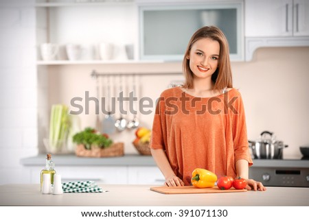 Young woman with fresh vegetables at table in the kitchen