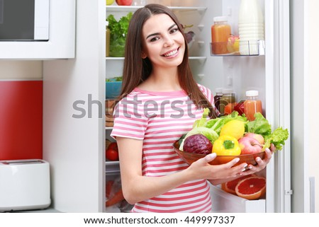 Young woman with fruits and vegetables beside fridge in kitchen