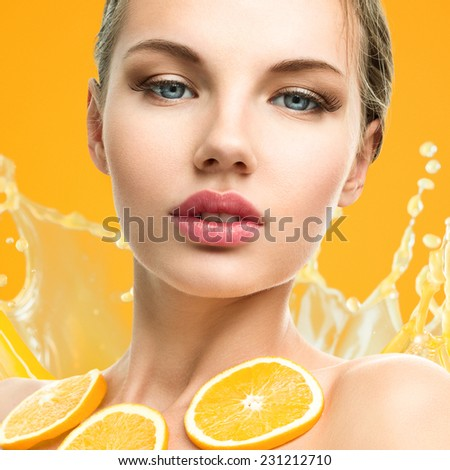 Young woman with fruits on bright orange background - stock photo