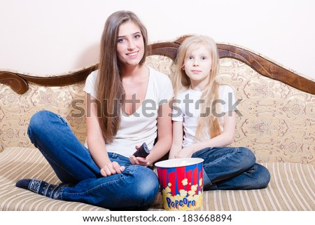 young woman with girl having fun sitting & watching movie, eating popcorn, happy smiling & looking at camera - stock photo