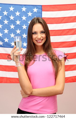 Young woman with glass of champagne on background of American flag