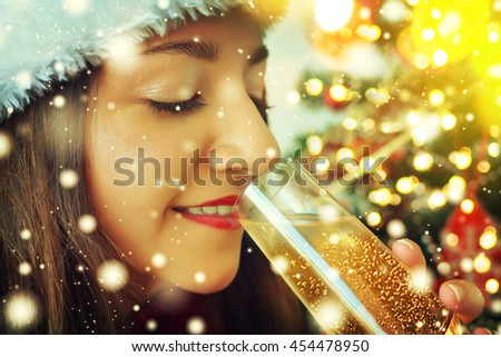 Young woman with glass of champagne with christmas tree on background
