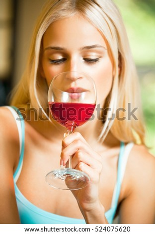 Young woman with glass of red wine, at home. Focus on glass. Caucasian blond model in home leisure and happiness concept.