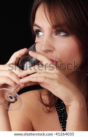 Young woman with glass of red wine, isolated on black background