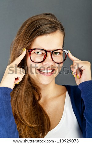 Young woman with glasses on black background