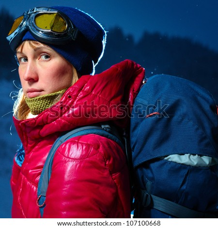 Young woman with goggles and backpack standing in winter dark forest and looking to a camera - stock photo
