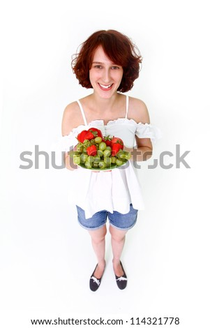 Young woman with grapes, apples and strawberries on a dish - stock photo