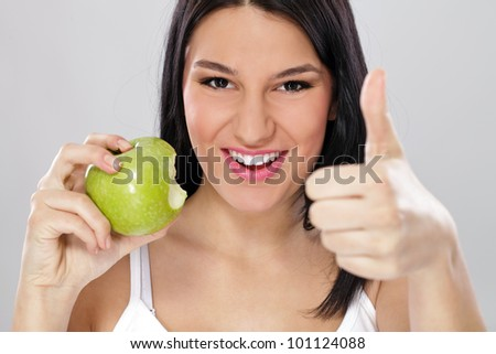 Young woman with green apple and showing thumb up, healthy eating - stock photo