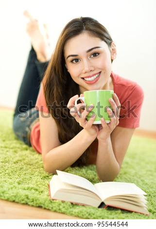 Young woman with green cup and book at home - stock photo