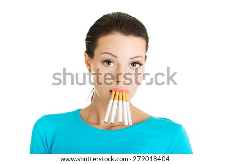 Young woman with group of cigarettes in mouth. - stock photo