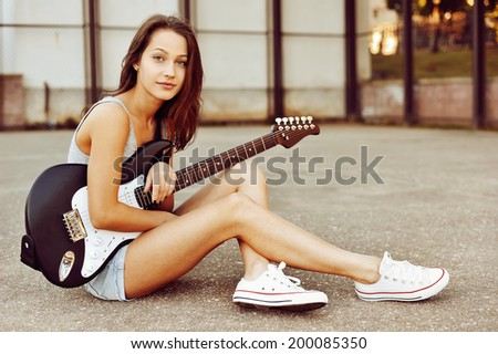 Young woman with guitar in summertime on sunset - stock photo