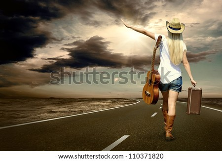 Young woman with guitar on the road and her vintage baggage - stock photo