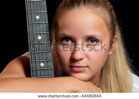 young woman with guitar over black background