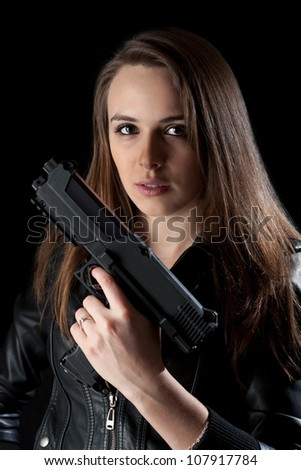 Young woman with gun in hand - stock photo