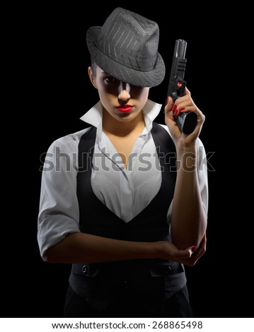 Young woman with gun on black - stock photo