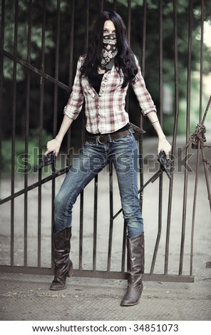 Young woman with guns. On metallic bar background. - stock photo