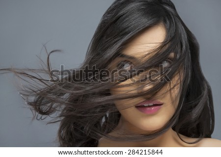 Young woman with hair blowing over face against colored background - stock photo