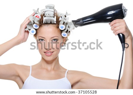 young woman with hair-curles and hairdryer doing hairstyle - isolated on white - stock photo
