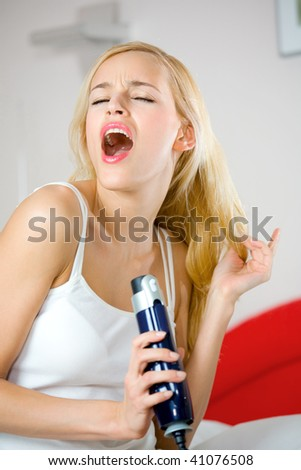 Young woman with hair dryer at bedroom