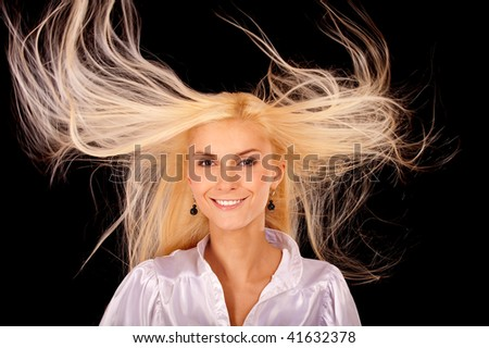 Young woman with hair fluttering on wind, it is isolated on black background. - stock photo