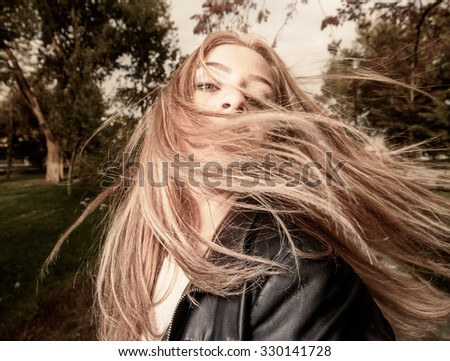 Young woman with hair swept by wind sepia toned image - stock photo