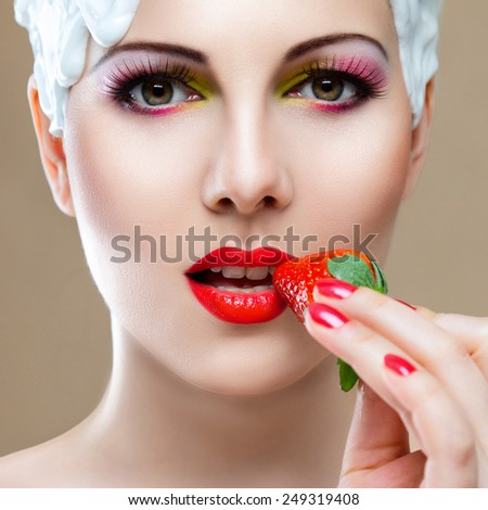 Young woman with hairstyle made from milk eating red ripe strawberry - stock photo