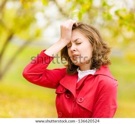 young woman with hand on forehead - stock photo