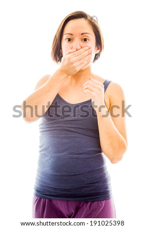 Young woman with hand over her mouth and shock - stock photo