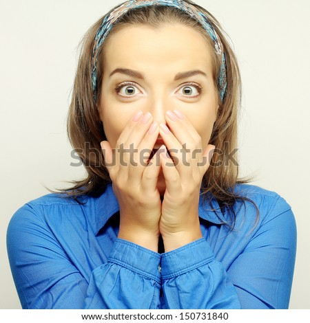 Young woman with hands over mouth. Surprise! - stock photo