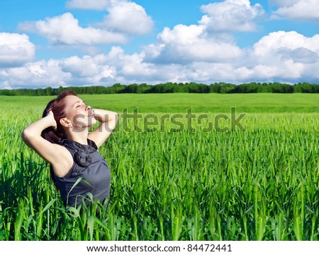 young woman with hands raised up in the wheat field