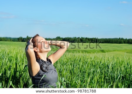 young woman with hands raised up in the wheat field over blue sky in summer - stock photo