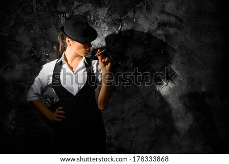 Young woman with hat and cigar on grey wall - stock photo