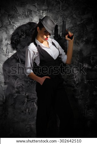 Young woman with hat and gun on grey wall - stock photo