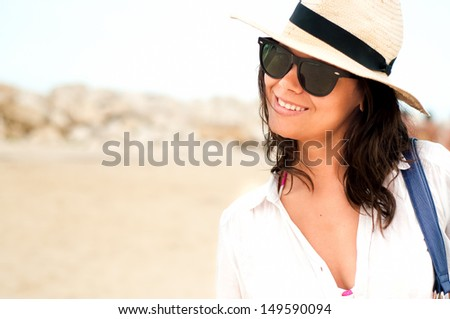 Young woman with hat enjoying the beach while on holiday in summer tropical resort - stock photo
