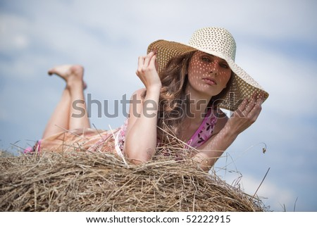 Young woman with hat lying on haystack.